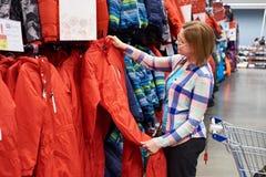 Kobieta wybiera narciarskiego kombinezon w sporta sklepie Zdjęcie Stock