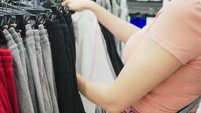 Kobieta wybiera nowego odziewa w dziecko sklepie odzieżowym zbiory