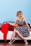 Kobieta wybiera rzeczy pakować w walizkę Obrazy Royalty Free