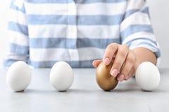 Kobieta wybiera złotego jajko od bielu przy stołem ones zdjęcie royalty free