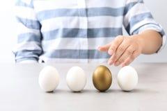 Kobieta wybiera złotego jajko od bielu przy stołem ones zdjęcie stock