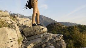 Kobieta wycieczkowicz iść na piechotę stojaki na krawędzi halnej falezy przeciw pięknemu góra szczytowi zdjęcie wideo