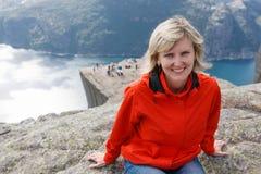 Kobieta wycieczkowicz na ambony skale, Preikestolen/, Norwegia Zdjęcie Royalty Free