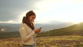 Kobieta wycieczkowicz używa jej telefon komórkowego przy zmierzchu halnego szczytu falezą zdjęcie wideo