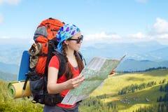 Kobieta wycieczkowicz w górach czyta mapę Obrazy Royalty Free