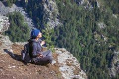 Kobieta wycieczkowicza obsiadanie na górze góry i relaksuje w pogodnym letnim dniu Zdjęcia Stock