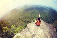 Kobieta wycieczkowicza use smartphone bierze fotografię na nadmorski góry wierzchołku Fotografia Stock