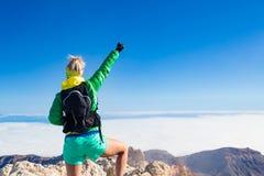 Kobieta wycieczkuje sukces ręki szeroko rozpościerać na góra wierzchołku Zdjęcie Stock