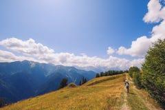 Kobieta wycieczkuje w górach i łąkach Svaneti park narodowy, Gruzja obraz royalty free