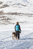 Kobieta wycieczkuje w zimie z psem Zdjęcia Royalty Free