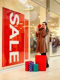 Kobieta wydawać pieniądzy dla robić zakupy przy zakupy centrum handlowym Zdjęcie Royalty Free
