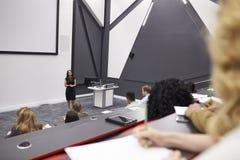 Kobieta wykładani ucznie w odczytowym theatre, w połowie rząd POV fotografia royalty free