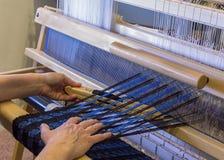 Kobieta wyplata wełna szalika na podłogowym krosienku Obrazy Stock
