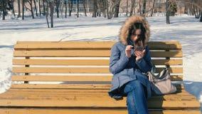 Kobieta wyszukuje internet na jej telefonu obsiadaniu na ławce w zimy miasta parku w słonecznym dniu zbiory wideo