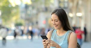 Kobieta wyszukuje telefon zawartość w ulicie zbiory