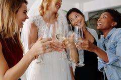 Kobieta wznosi toast szampańskich szkła z przyjaciółmi w bridal todze obraz royalty free