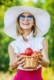 Kobieta z łozinowym koszem trzyma czerwonych jabłka Zdjęcie Stock