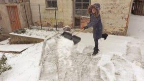 Kobieta z śnieżną łopatą czyści podwórze blisko starej stajni zbiory