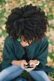 Kobieta z afro włosianym stylem texting na smartphone zdjęcie stock