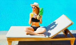 kobieta z ananasem pije owocowego sok od filiżanki na deckchair nad błękitne wody basenu tłem zdjęcie royalty free