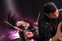 Kobieta z bębenami ustawia bawić się hard rock muzykę na scenie Obrazy Stock