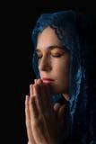 Kobieta z błękit głowy szalikiem nad jej głową modli się pokój obraz stock