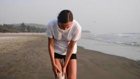 Kobieta z bandażem na zdradzonym kolanie biega na piaskowatej plaży zbiory wideo