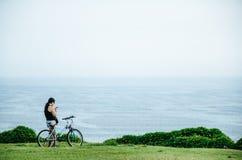 Kobieta z bicyklem przed morzem Zdjęcia Stock