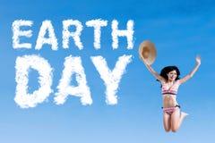 Kobieta z bikini i Ziemskiego dnia tekstem Fotografia Royalty Free