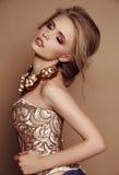 Kobieta z blondynem w eleganckiej złotej sukni i luksusowej kolii Zdjęcie Royalty Free