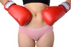 Kobieta z bokserskimi rękawiczkami walczy z jej brzuchem, diety pojęcie Zdjęcia Stock