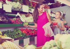 Kobieta z córką wybiera paprykę w karmowym sklepie Zdjęcie Stock