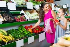 Kobieta z córką wybiera zieloną i czerwoną paprykę Zdjęcie Stock