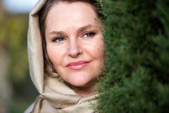 Kobieta z chustka na głowę obok drzewa Obrazy Stock