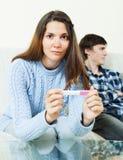 Kobieta z ciążowym testem przeciw nieszczęśliwemu chłopakowi Zdjęcia Stock