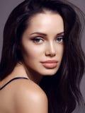 Kobieta z ciemnym włosy i powabnym uśmiechem z perfect rozjarzoną skórą, zdjęcie royalty free