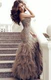 Kobieta z ciemnym włosy w luksusowego cekinu smokingowy pozować na schodkach Obrazy Stock