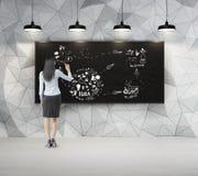 Kobieta z czarni włosy rysuje nakreślenie w zmroku betonu pokoju wi zdjęcia royalty free