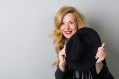 Kobieta z czarnym kapeluszem na szarości Fotografia Royalty Free