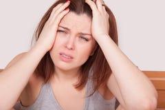 Kobieta z czerwonym nosem i cierpienie od okropnej migreny w łóżku Obrazy Stock