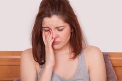 Kobieta z czerwonym nosem i cierpienie od okropnej migreny w łóżku Zdjęcia Royalty Free