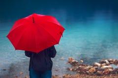 Kobieta z czerwonym parasolem kontempluje na deszczu obrazy stock