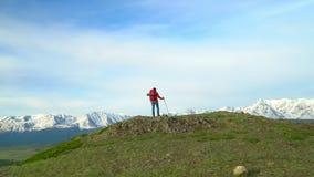 Kobieta z czerwonym plecakiem iść w górę zieleni żal Widok śnieżne góry zbiory wideo