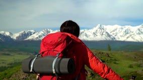 Kobieta z czerwonym plecakiem iść w górę zieleni żal Widok śnieżne góry zbiory