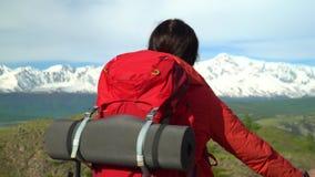 Kobieta z czerwonym plecakiem iść w górę zieleni żal Widok śnieżne góry zdjęcie wideo