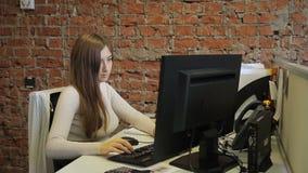 Kobieta z czerwonym włosy pracuje przy komputerowym pobliskim ściana z cegieł zdjęcie wideo