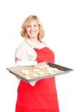 Kobieta z czerwonymi fartuch teraźniejszości bożych narodzeń ciastkami obrazy royalty free