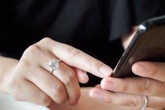 Kobieta z diamentowym pierścionkiem na ręce używać smartphone w restauraci zdjęcie royalty free