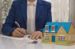 Kobieta z domu modelem i pióra podpisywania kontrakta dokumentem Obrazy Royalty Free