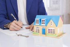 Kobieta z domu modelem i pióra podpisywania kontrakta dokumentem Zdjęcie Royalty Free